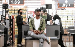 A shopper sitting by a supermarket check out